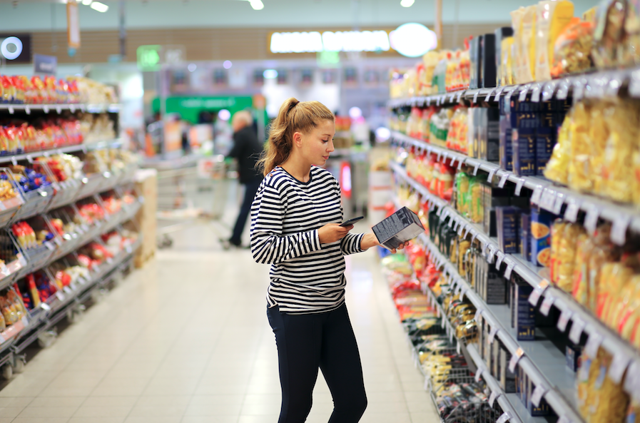 Woman grocery shopping looking at nutrition label