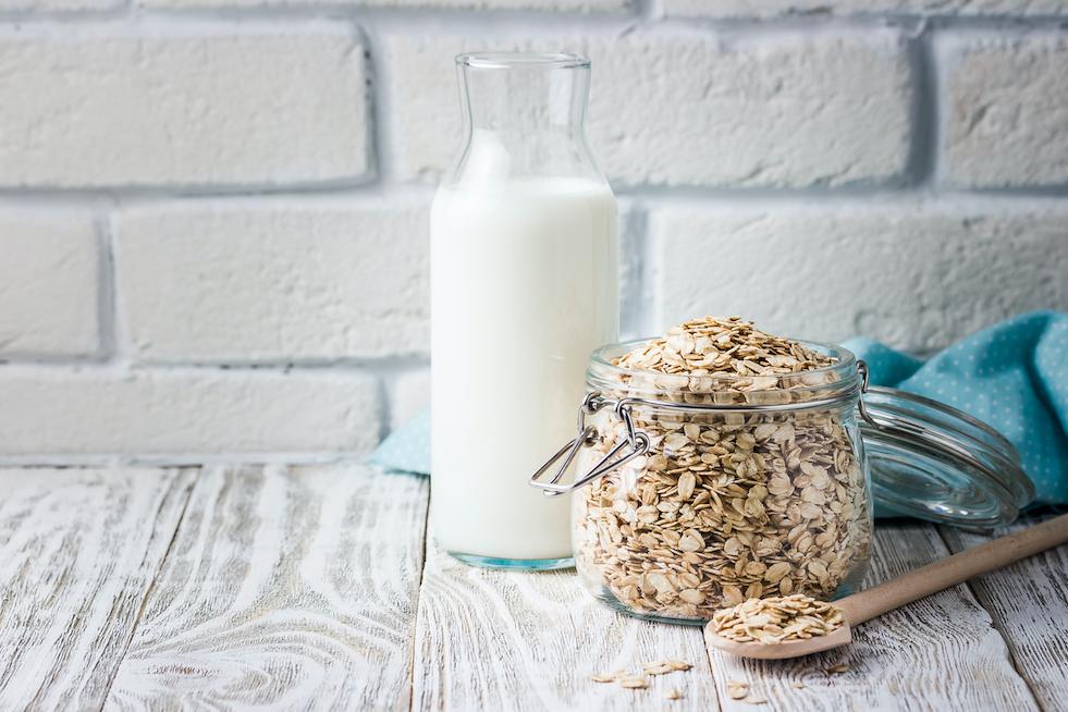 oat milk sitting next to jar of oats