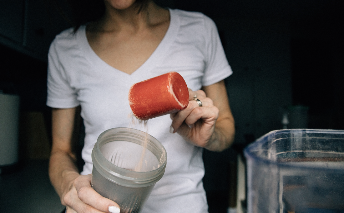 woman pouring protein powder into protein drink
