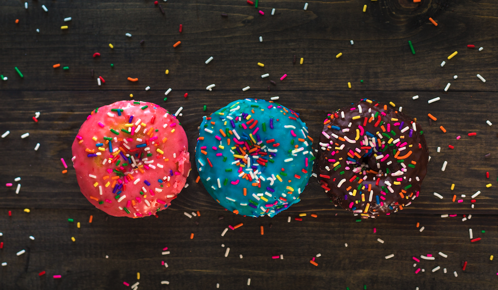 three donuts and sprinkles on wood background